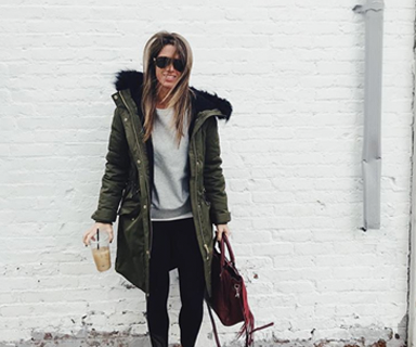 Crystal Seaver outside wearing a long coat holding an ice coffee